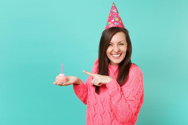 파란색 벽 배경 스튜디오 초상화에 격리된 손에 촛불을 들고 케이크에 검지 손가락을 가리키는 니트 분홍색 스웨터 생일 모자를 쓴 재미있는 젊은 여성. 사람들이 라이프 스타일 개념입니다. 복사 공간을 비웃습니다.