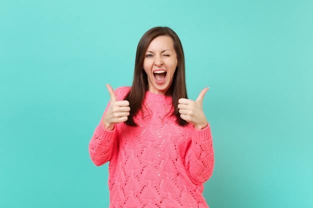 Смешная молодая женщина в вязаном розовом свитере мигает и показывает большие пальцы руки вверх, изолированные на синем фоне бирюзовой стены, студийный портрет. люди искренние эмоции, концепция образа жизни. копируйте пространство для копирования.