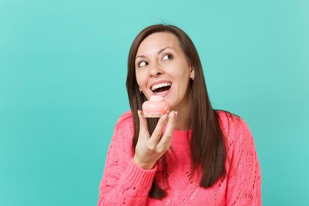 Смешная молодая женщина в вязаном розовом свитере, глядя вверх, держа в руке торт, изолированный на синем фоне бирюзовой стены, студийный портрет. люди искренние эмоции, концепция образа жизни. копируйте пространство для копирования.