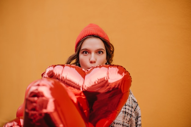 빨간 모자에 재미 있은 젊은 여자는 거대한 광택 풍선으로 그녀의 얼굴의 일부를 다룹니다