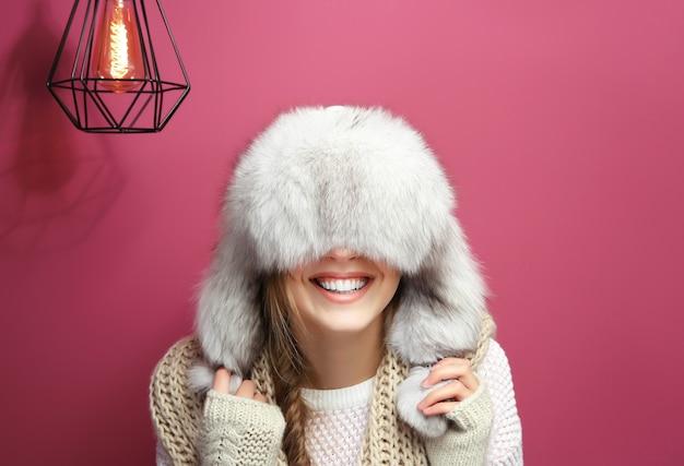 色の背景に暖かい服を着た面白い若い女性