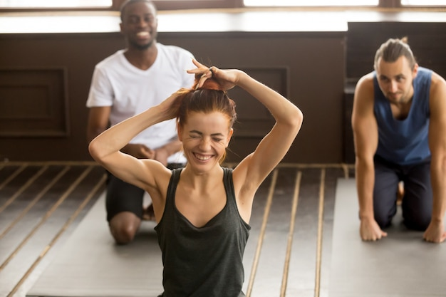 Funny young woman laughing at multi-ethnic group fitness yoga cl