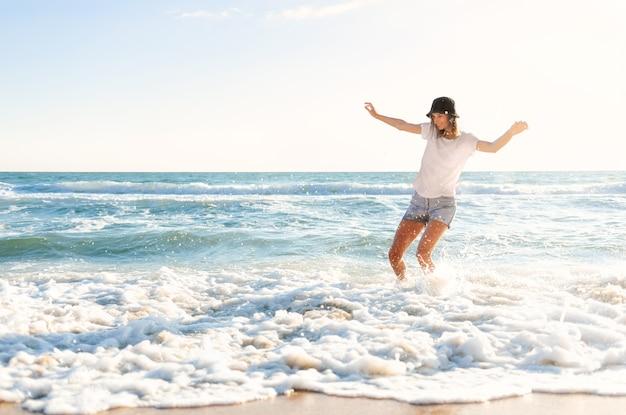 水しぶきを楽しんでいる青い海の海岸で面白い若い女性