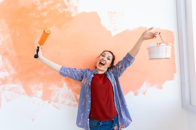 彼女の新しいアパートの壁を描く面白い若い女性