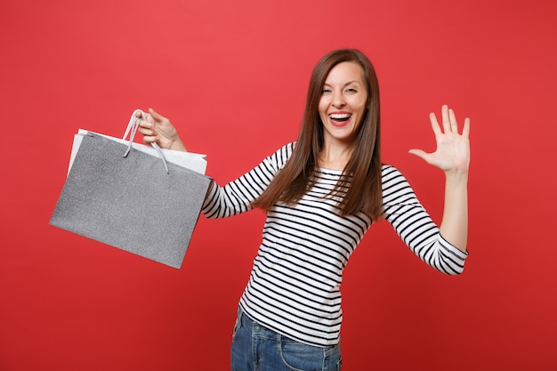 Funny young woman showing palm, waving hand, holding packages bags with purchases after shopping isolated on bright red wall background. people sincere emotions, lifestyle concept. mock up copy space.