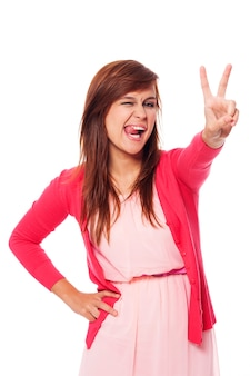 Смешная молодая женщина показывает знак победы