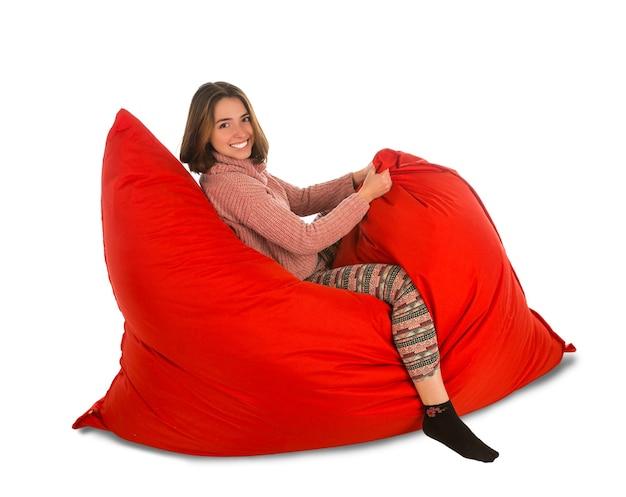 居間または白で隔離される他の部屋のための赤いお手玉ソファの椅子に座っている面白い若い女性