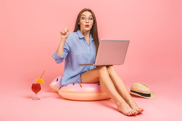 Funny young woman in swimsuit working on laptop