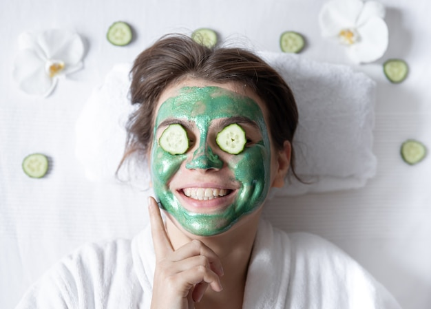 彼女の顔に化粧マスクと彼女の目にきゅうりを持つ面白い若い女性