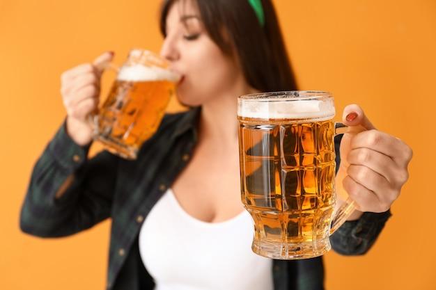 ビールと面白い若い女性。聖パトリックの日のお祝い