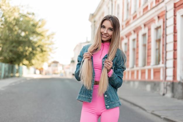 빈티지 건물 근처 도시에서 포즈를 취하는 유행 여름 옷에 긍정적 인 미소로 세련된 금발 긴 머리를 가진 재미있는 젊은 여자. 행복한 소녀. 여름 스타일. 여성 의류의 새로운 컬렉션.