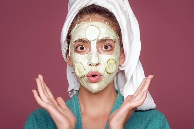 얼굴에 오이 마스크와 함께 재미있는 젊은 여자. 회춘, 건강, 젊음. 뷰티 살롱 개념. 피부 및 모발 관리, 스파, 웰빙. 머리에 목욕 타월로 소녀입니다.