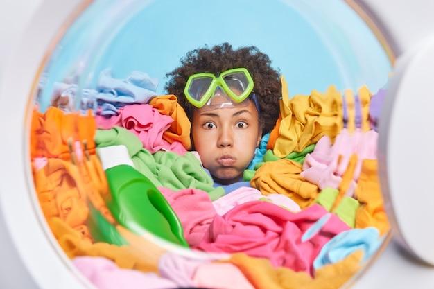 곱슬머리를 한 재미있는 젊은 여성은 이마에 스노클링 마스크를 쓰고 여러 가지 빛깔의 세탁실 파란색 벽 주위에서 뺨을 불고 있다