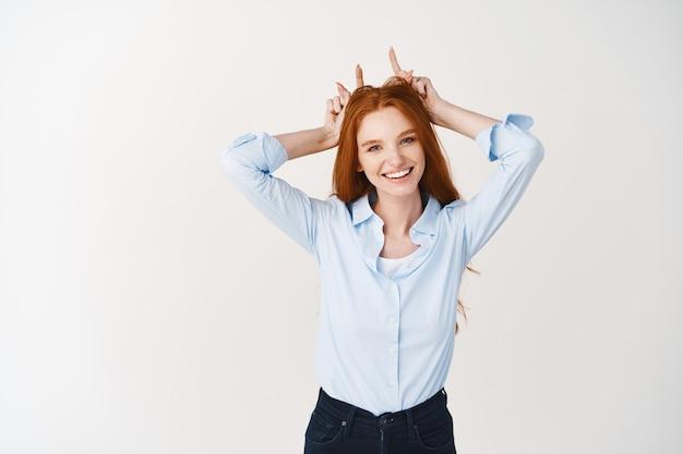 진저 머리와 주근깨를 가진 재미있는 젊은 여성이 머리에 손가락을 대고 웃고, 흰 벽 위에 서 있는 악마 뿔을 보여줍니다.