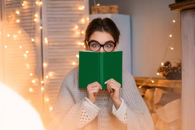 Giovane donna divertente con gli occhiali sulle ghirlande di luce che tiene un libro tra le mani e legge