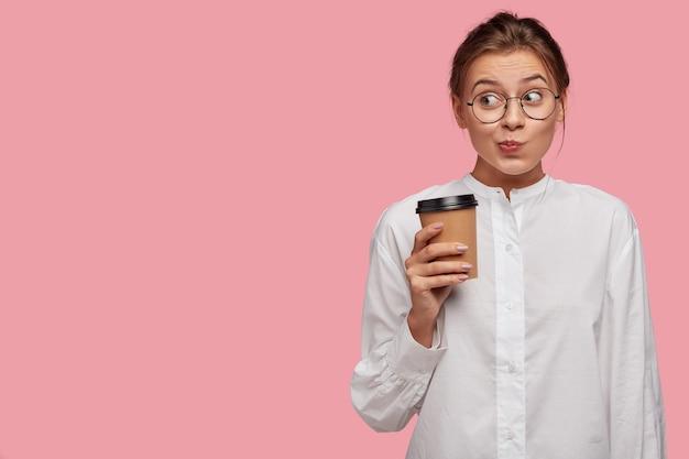 ピンクの壁にポーズをとって眼鏡をかけて面白い若い女性