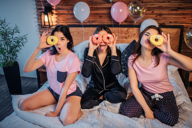 Funny young women playing on bed in room. they coveres eyes with dounts. women wear pajamas. they have party in festive room.