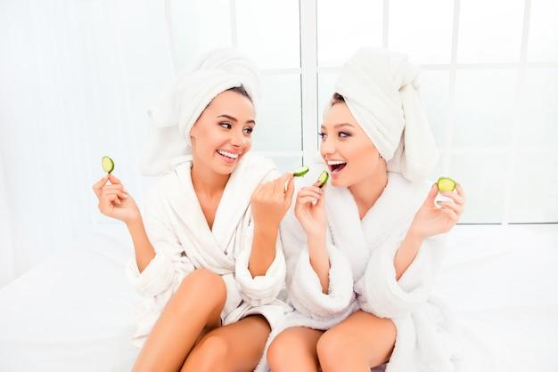 頭にタオルを持った面白い若い女性が、キュウリのスライスを他の人に食べさせます