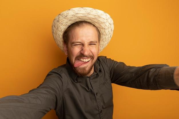 회색 셔츠와 여름 모자에 funy 젊은 잘 생긴 남자 혀를 튀어 나와 얼굴을 찡 그리기 만들기
