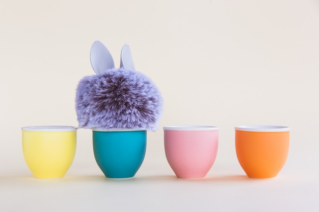 Fur ball with bunny rabbit ears in egg stand on bright background. four egg stands
