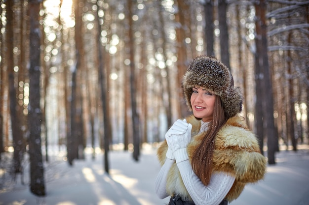 Fur vest and winter hat on beautiful young caucasian woman in winter sunny forest