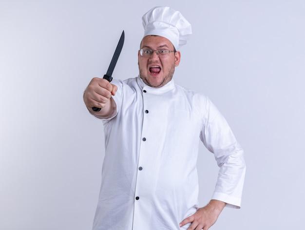 白い壁に隔離された正面に向かってナイフを伸ばして正面を見て腰に手を保ちながらシェフの制服と眼鏡を身に着けている猛烈な大人の男性料理人