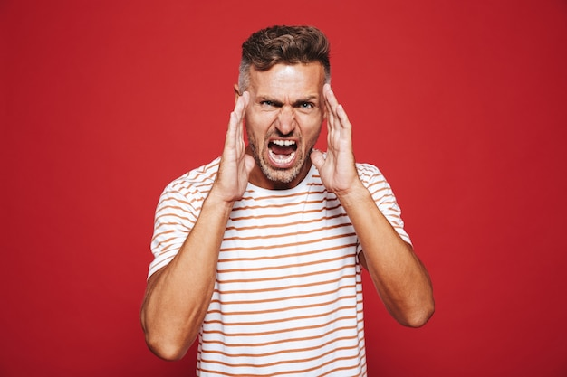 Furious adult man in striped t-shirt screaming and touching face isolated on red