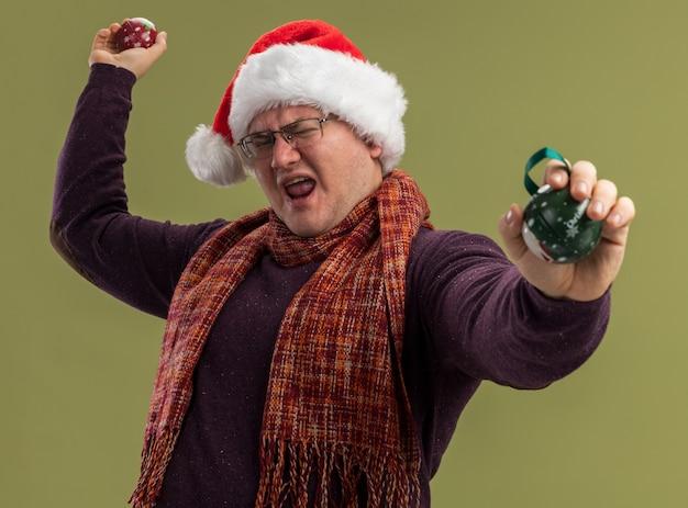 Furioso uomo adulto che indossa occhiali e cappello da babbo natale con sciarpa intorno al collo che allunga le palline di natale isolate su muro verde oliva green