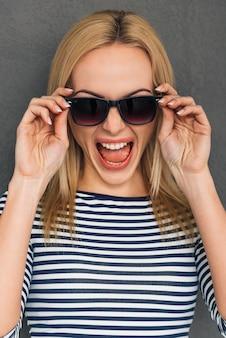 激怒し、感情的。彼女のサングラスを調整し、灰色の背景に立っている間口を開いたままにしておく美しい若い女性