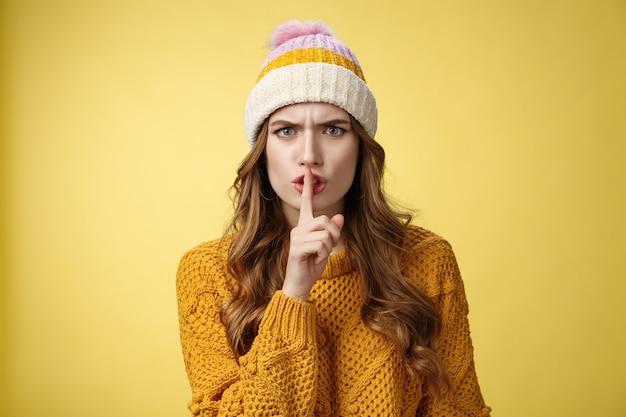Furioso arrabbiato infastidito donna carina che ti zittisce irritato parlare ad alta voce durante un incontro importante accigliato rannicchiato incazzato mostrando shhh gesto dito indice bocca premuta, sfondo giallo