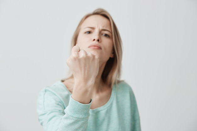 Furious angry displeased young caucasian female frowns face in displeasure, shows clenched fists, demonstrates strength and irritation, annoyed with someone. negative emotions concept.