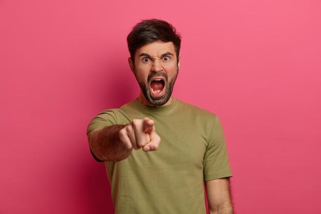 猛烈な怒りの無精ひげを生やした男は気性を失い、狂気になり、イライラして悲鳴を上げてあなたを指さし、誰かを非難し、否定的な感情を表現し、カジュアルな服を着て、ピンクの壁に隔離されます