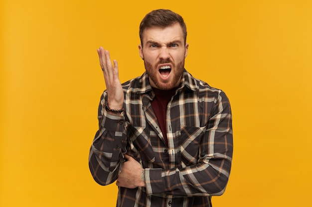 Furious angry young man in plaid shirt with beard and raised hand looks aggressive shouting and arguing over yellow wall