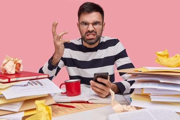 Furious bearded young guy gestures with hand, angry to recieve spam on cell phone, wears glasses, black and white striped jumper