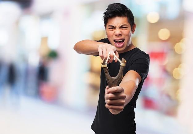 그의 새총을 가지고 노는 분노 소년