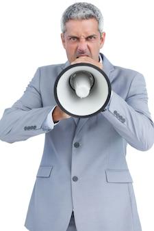 Неистовый бизнесмен позирует с громкоговорителем и смотрит на камеру