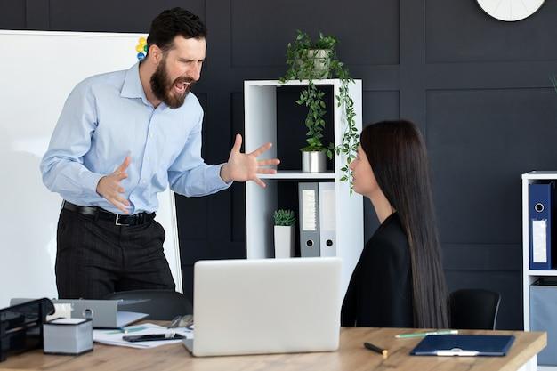Разъяренный бизнесмен кричит на сотрудницу, работающую в общем офисе
