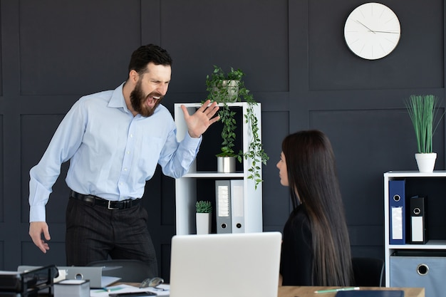 Furious businessman shout at female employee working in shared office