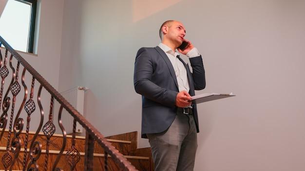 残業している金融会社の階段に立ってスマートフォンで話している猛烈なビジネスマン。現代の金融ビルで働くプロの成功したビジネスマンのグループ。