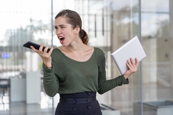 Furious businesswoman yelling at partner on speakerphone