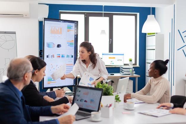 Furioso manager aziendale che chiede spiegazioni a colleghi multietnici che tengono un rapporto finanziario nella sala conferenze