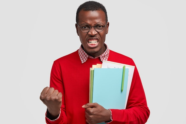Furious dark skinned man clenches fists, shows white teeth, carries textbooks, feels annoyed with something bad
