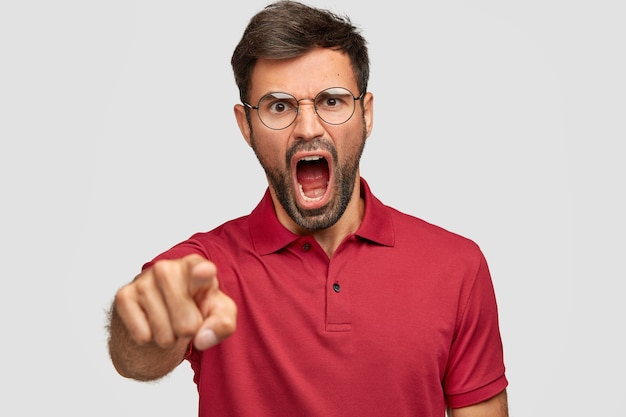 Разъяренный подавленный мужчина с темной щетиной, сердито кричит на кого-то, указывает, одетый в ярко-красную футболку, изолированный над белой стеной. небритый сумасшедший выражает ярость, громко кричит