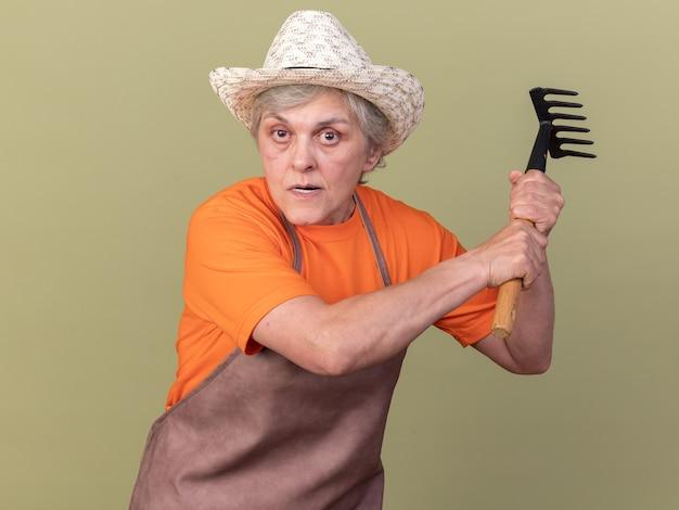 Giardiniere femmina anziano furioso che indossa il cappello da giardinaggio che tiene rastrello