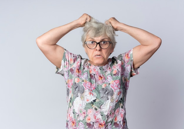 Furious elderly woman in optical glasses holds and lifts hair looking isolated on white wall