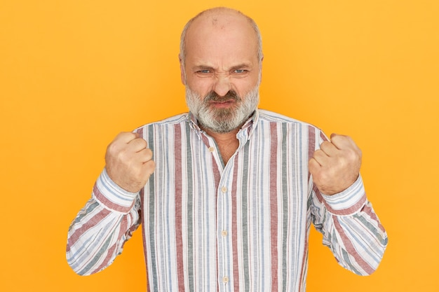 灰色のひげが顔をゆがめ、拳を握りしめ、否定的な感情を表現している激怒した祖父