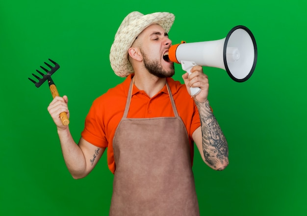 Giardiniere furioso uomo che indossa il cappello da giardinaggio tiene il rastrello e grida in altoparlante