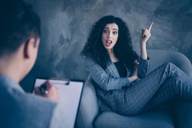 분노한 소녀가 의자에 앉아 회색 배경 위에 삶의 문제에 대해 심리학자에게 이야기합니다.