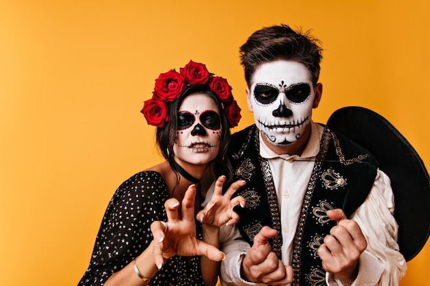 Furious guy and girl with halloween makeup posing for close-up portrait in orange wall.