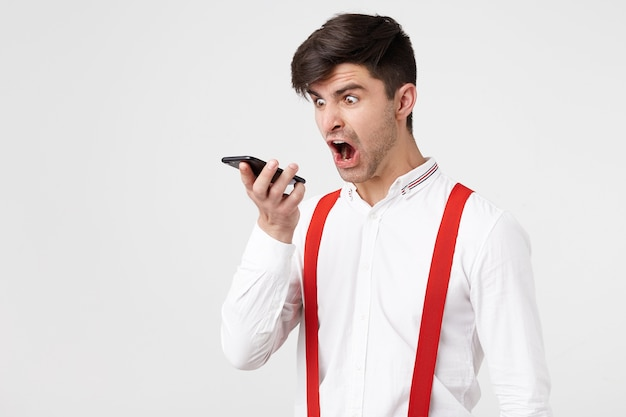 Furious handsome man is screaming on someone via telephone conversation